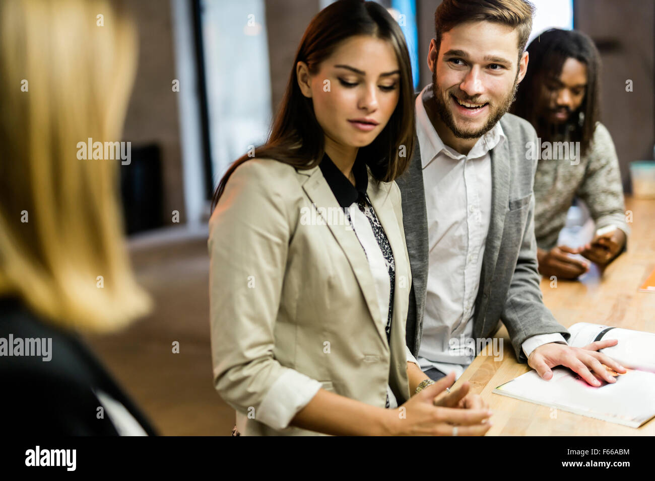 Man flirting with another woman in a bar while his girlfriend is present - Stock Image