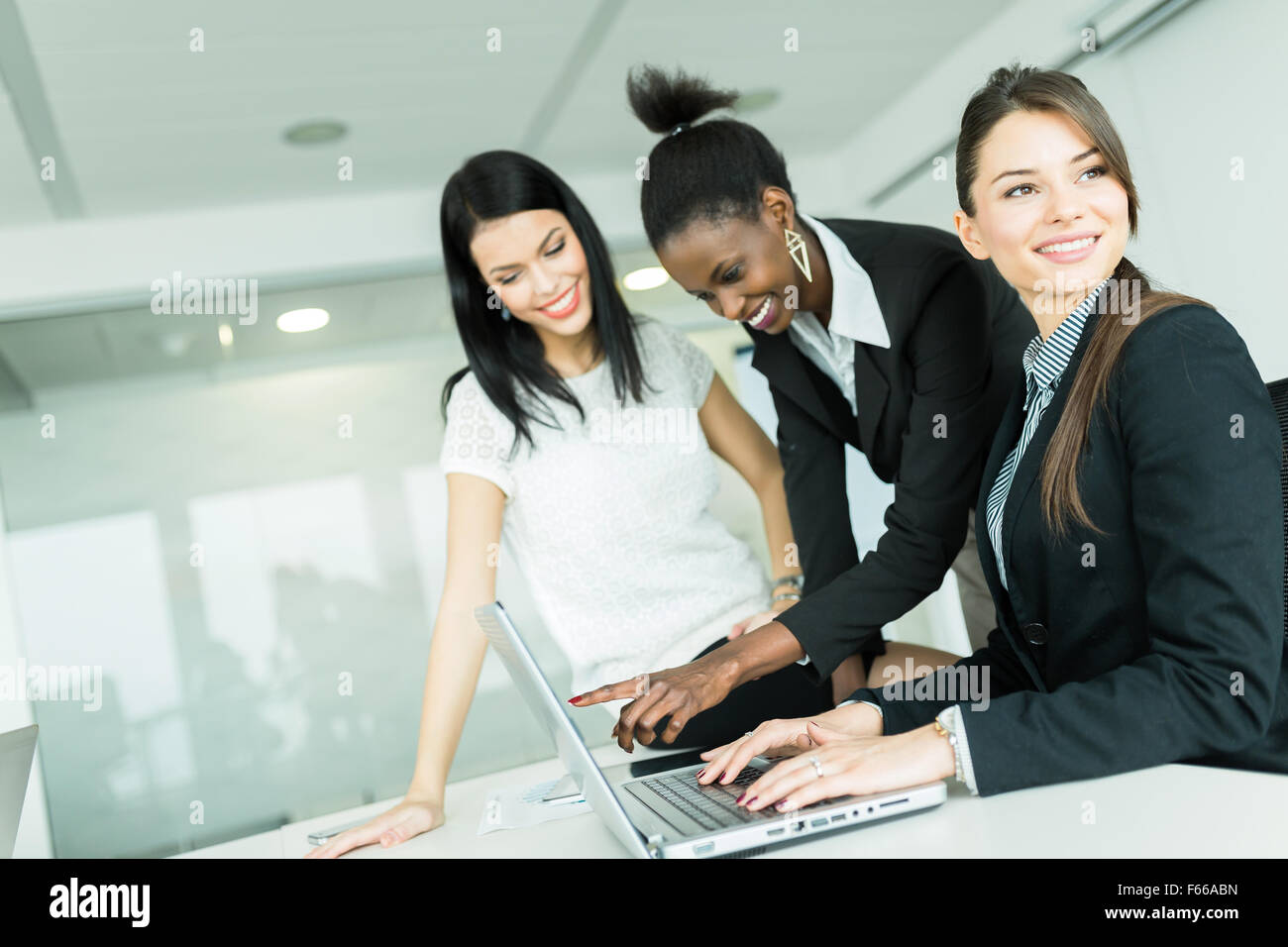 Businesswomen exchanging thoughts in a nice office environment while working on a laptop - Stock Image