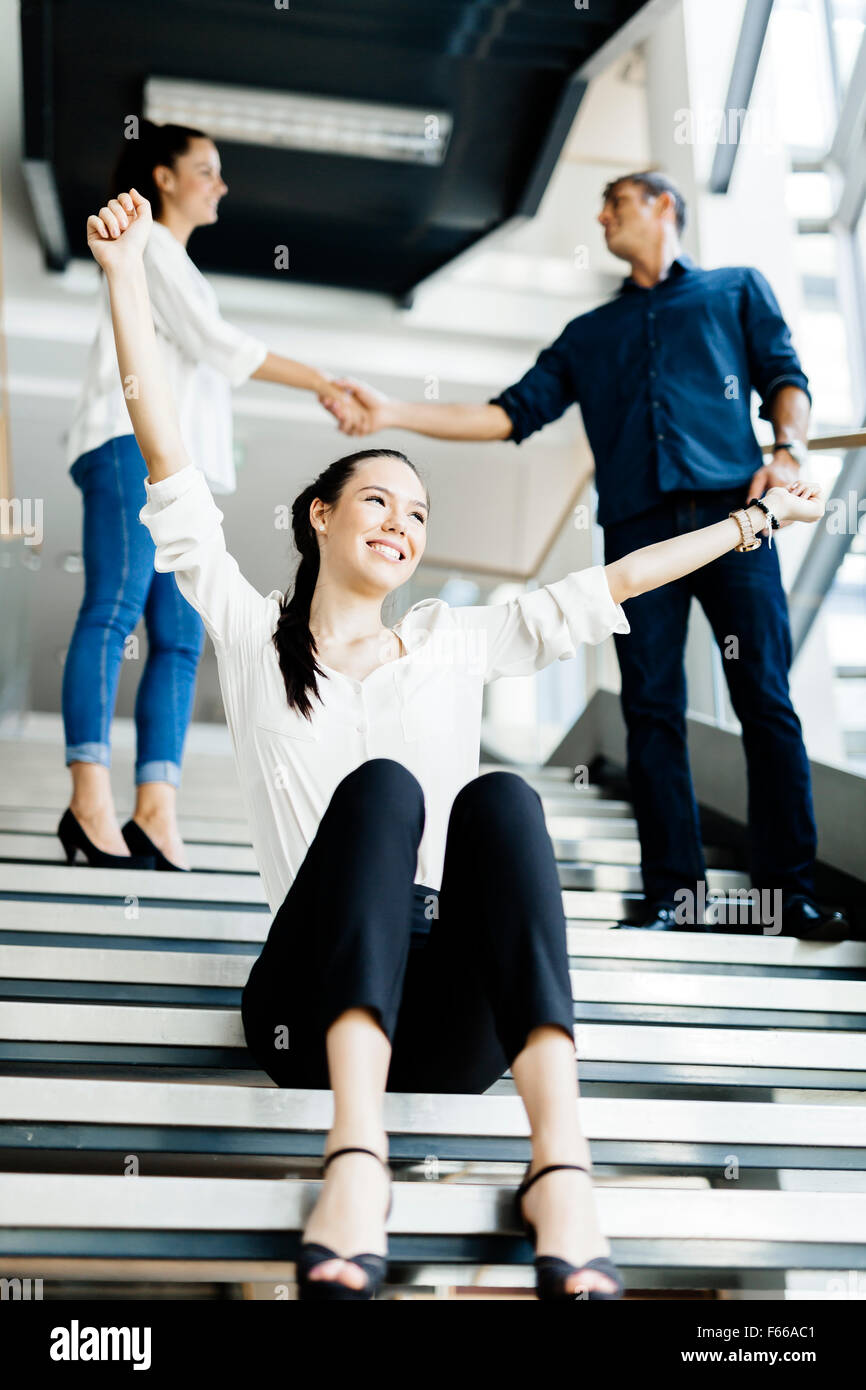 Group of business people shaking hands on stairs in a beautiful modern office and being happy - Stock Image