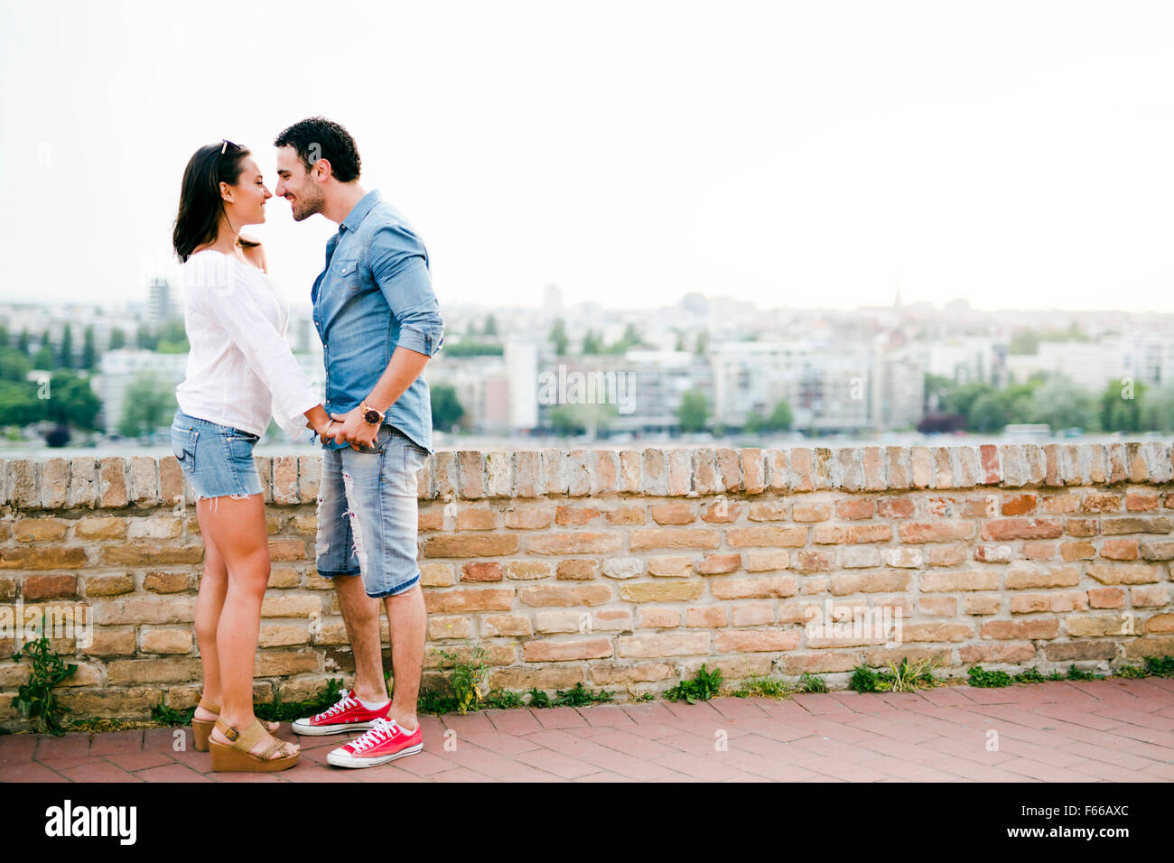 Young and beautiful couple in love being close to each other outdoors and about to kiss - Stock Image