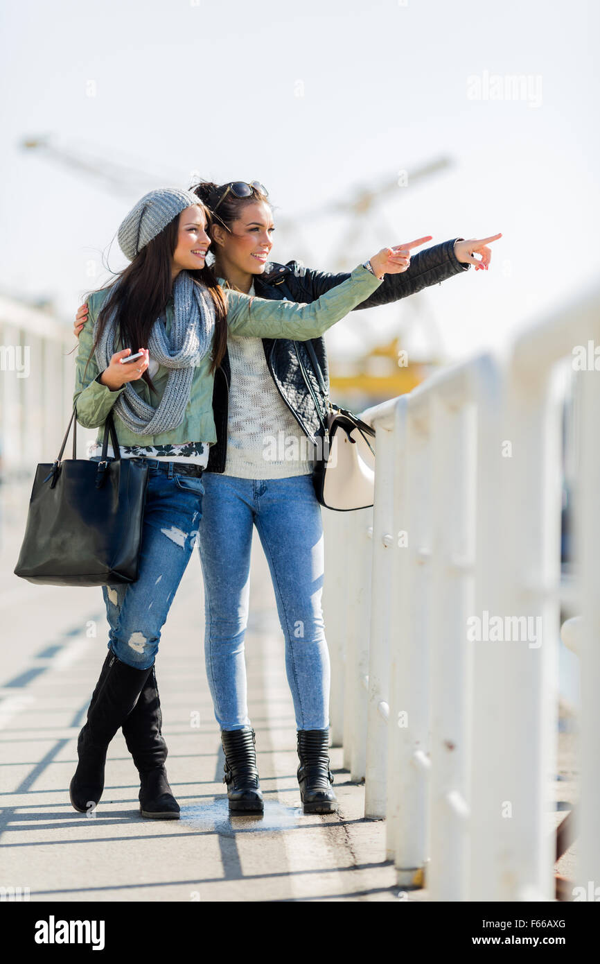 Two young and beautiful women looking over a dock fence and pointing in a direction - Stock Image
