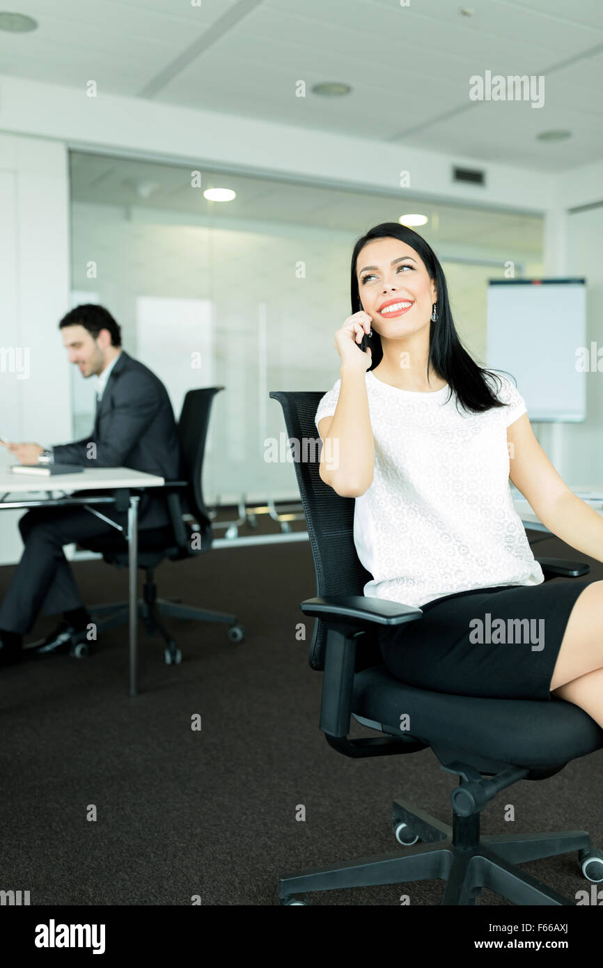 Businesswoman and a businessman working in an nice office  while sitting in chairs at their desks - Stock Image