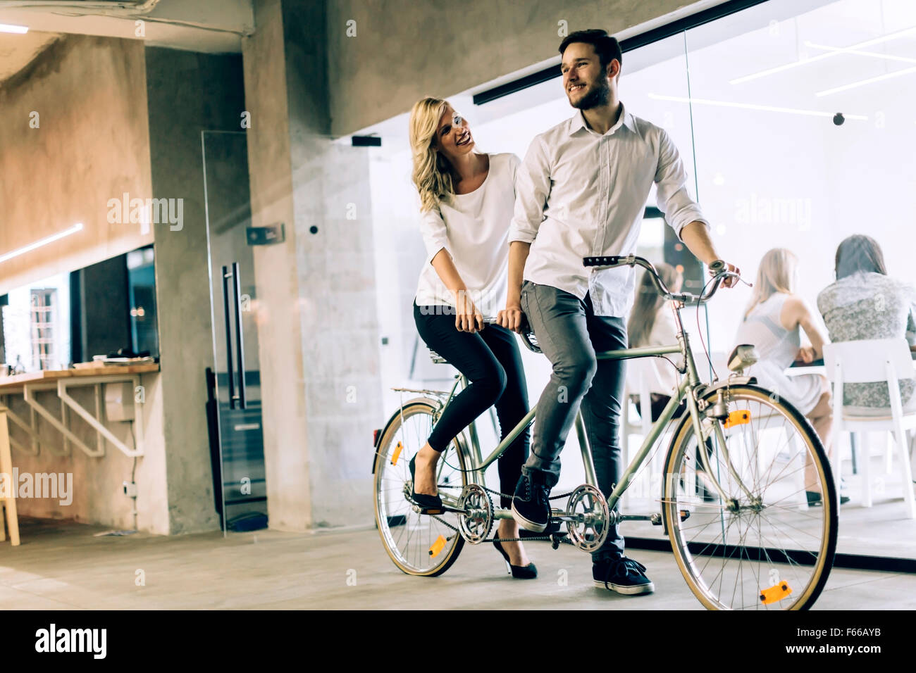 Business people on twin bicycle with mutual goals and same vision in business - Stock Image