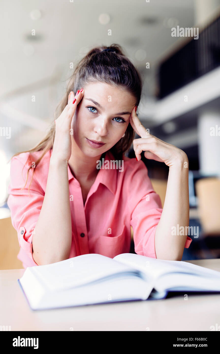 Female student studying and reading in a library but is having a hard time understanding the material - Stock Image