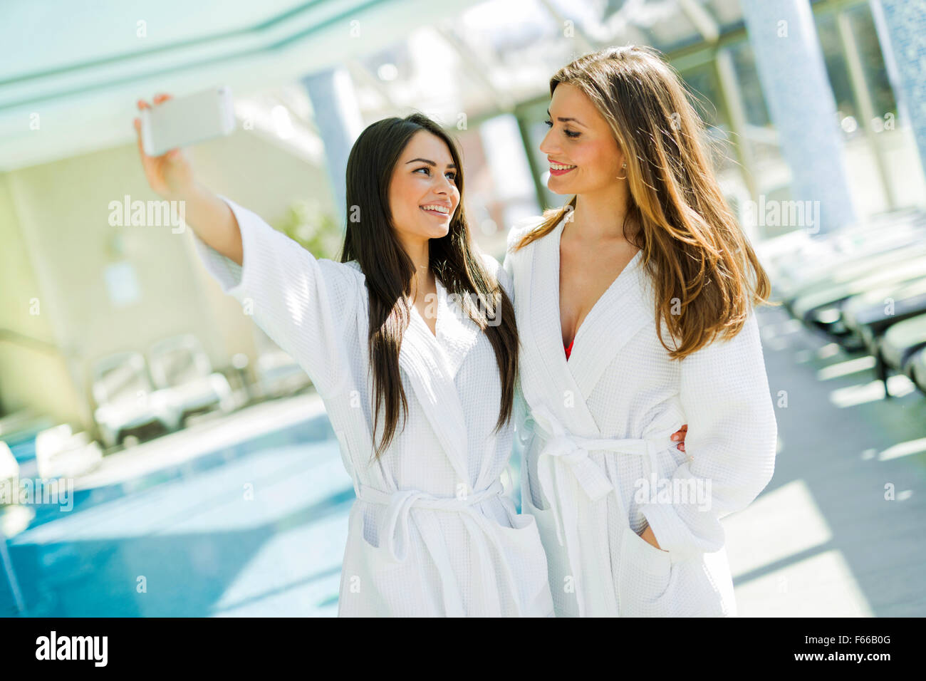 Two beautiful girls  taking a selfie next to a swimming pool - Stock Image
