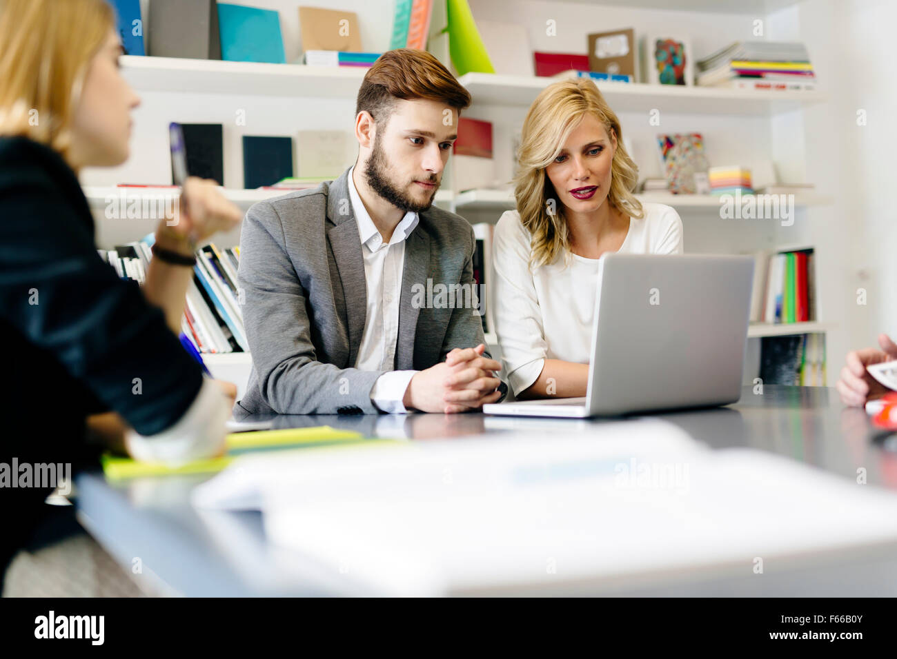 Businessman and businesswoman working together in office as part of a team and consulting with colleagues - Stock Image