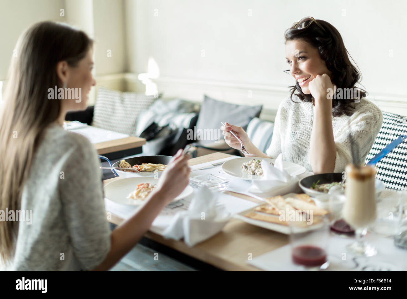 Two beautiful young women eating in a restaurant while having a conversation - Stock Image