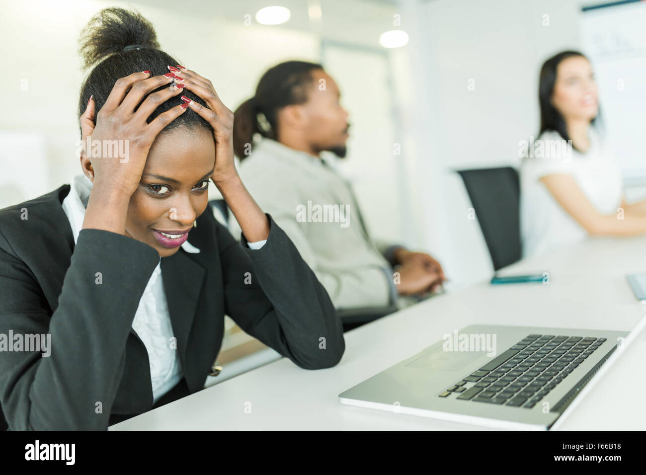 Young stressed businesswoman battling with a migraine during a business conference - Stock Image