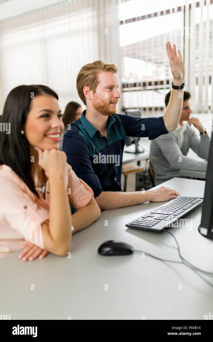 Beautiful young woman and a man raising hands in classroom in  while sitting in fron of a desktop - Stock Image