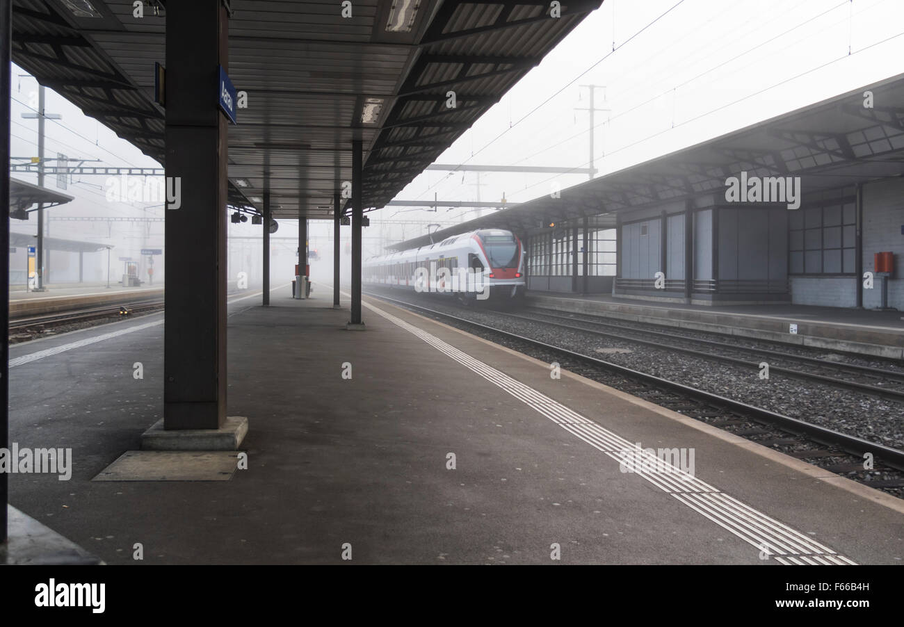 Platform of the train station of Aarau, Switzerland, on a dull foggy morning. - Stock Image