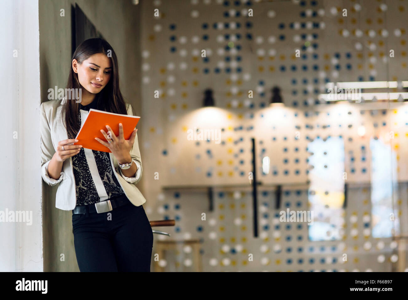 Businesswoman reading a document in modern office - Stock Image