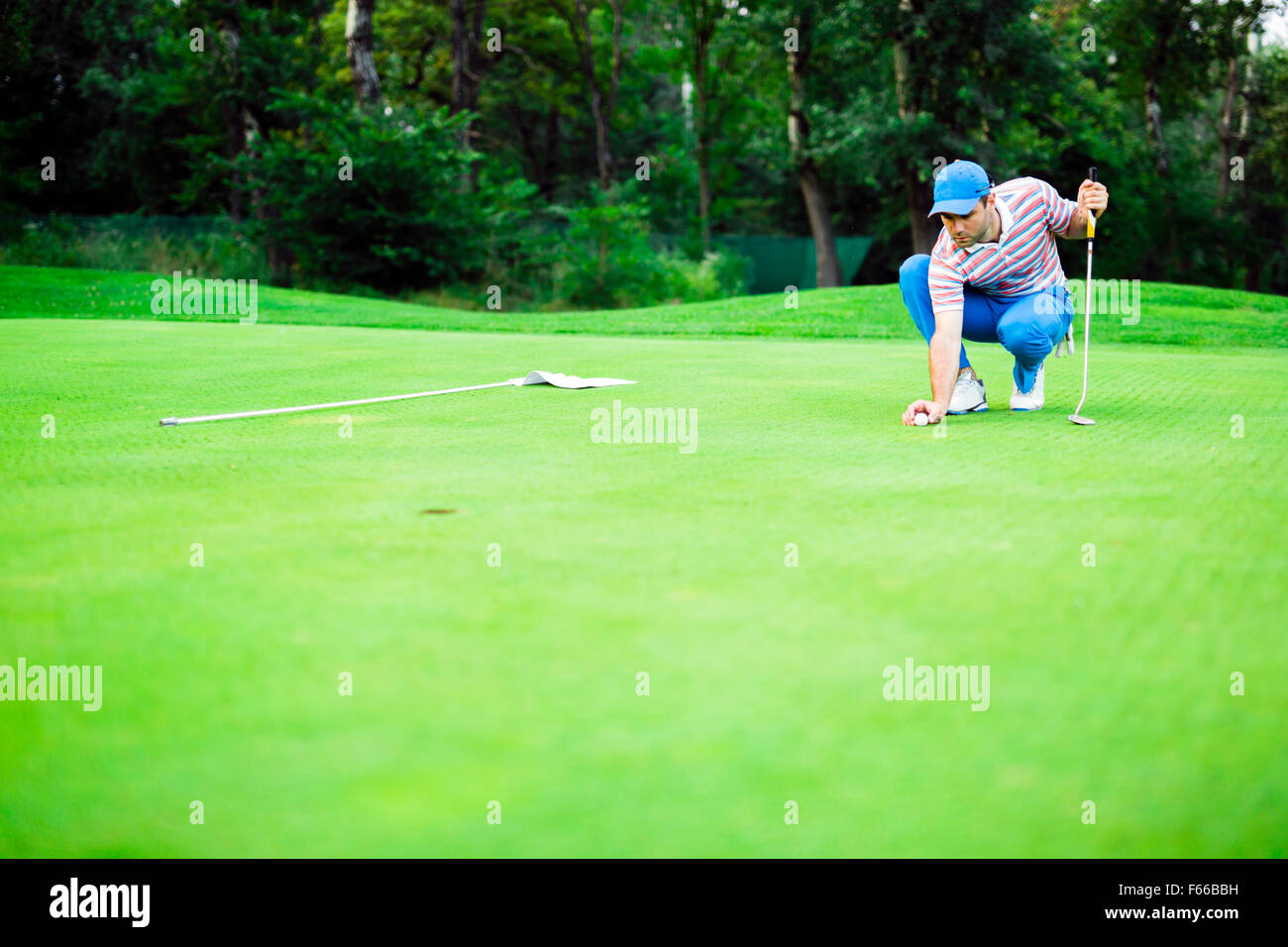 Golf player marking ball on the putting green before lifting the ball - Stock Image