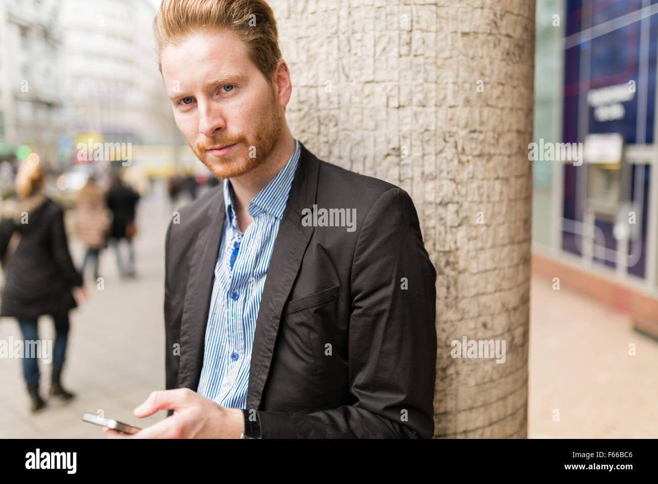 Portrait of a businessman while holding a cell phone in a busy city - Stock Image