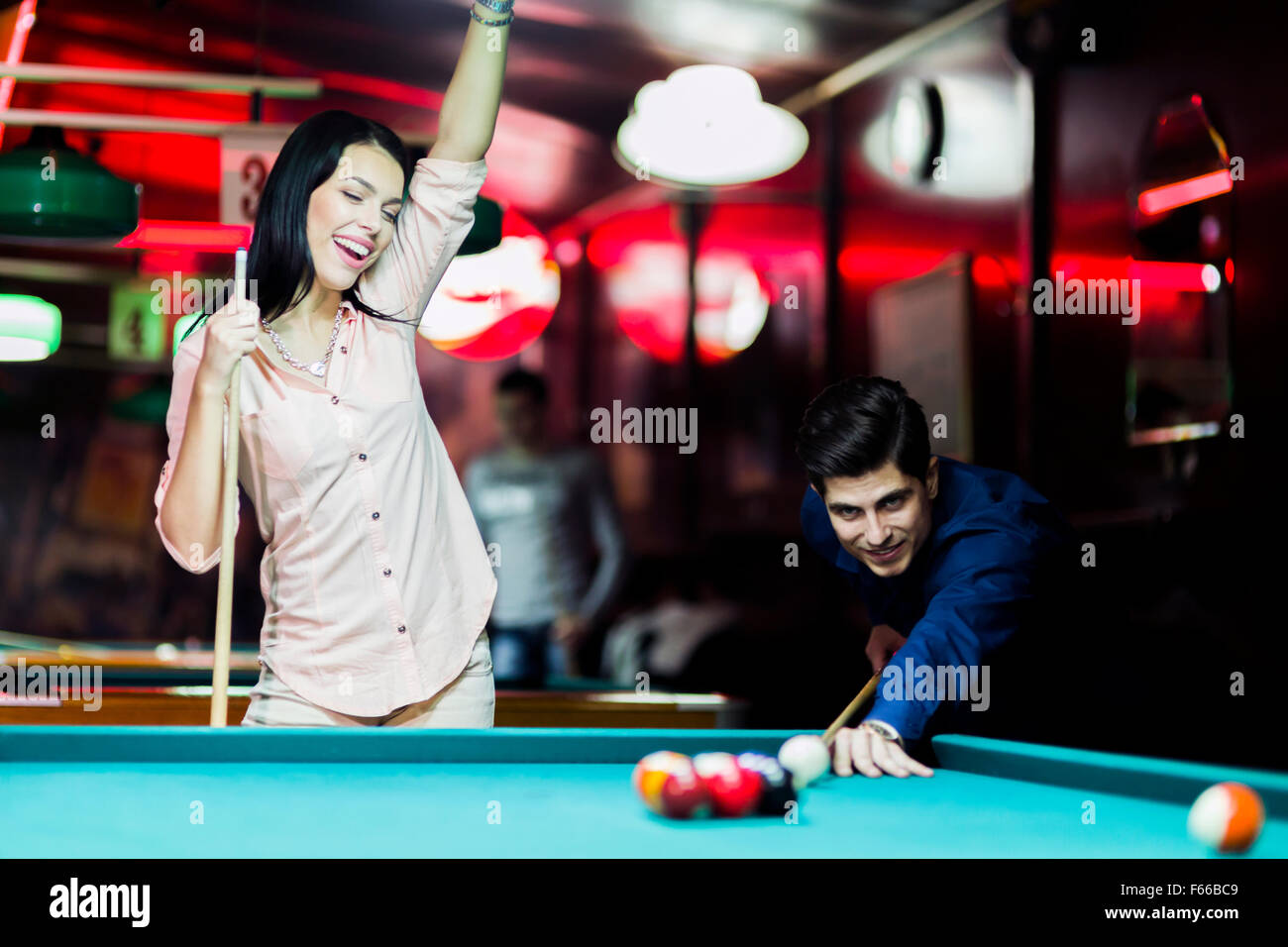 Young people playing billiard in a club pub bar - Stock Image