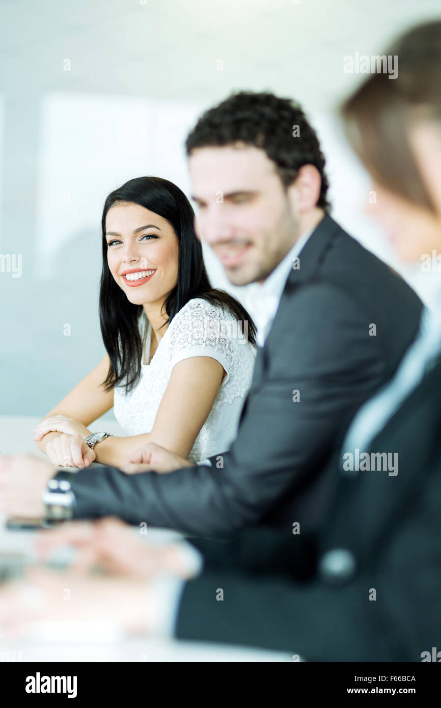 Young business people waiting for a  conference to commence - Stock Image