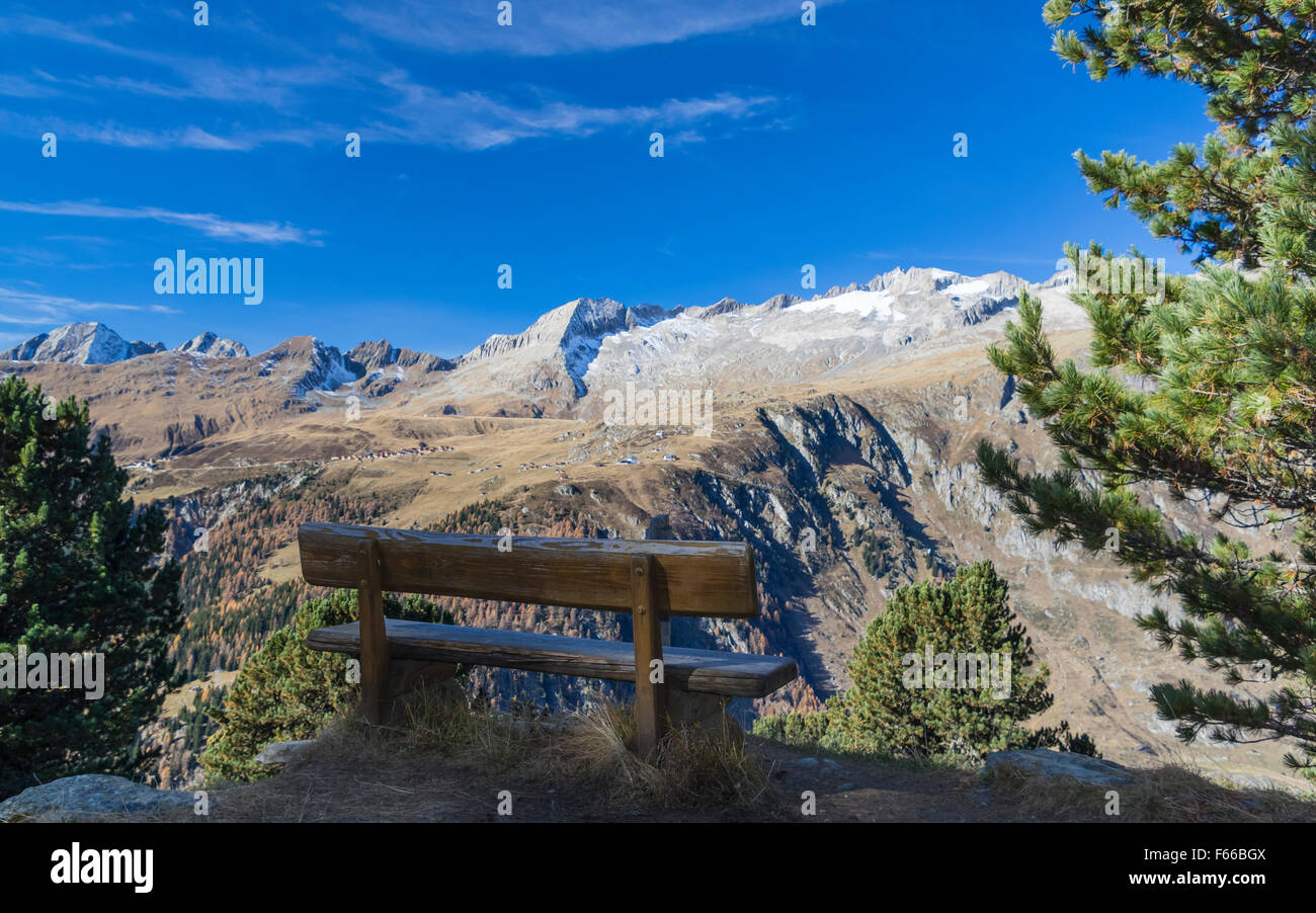 A bench in an Alpine region of Valais, Switzerland, with a splendid view of the settlement of Belalp and the mountains. - Stock Image