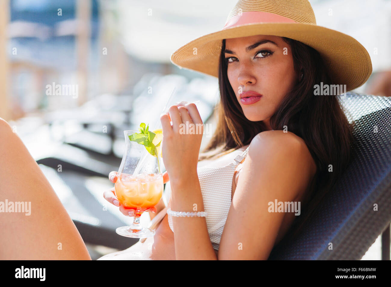 Portrait of a beautiful woman drinking cocktails while sunbathing - Stock Image