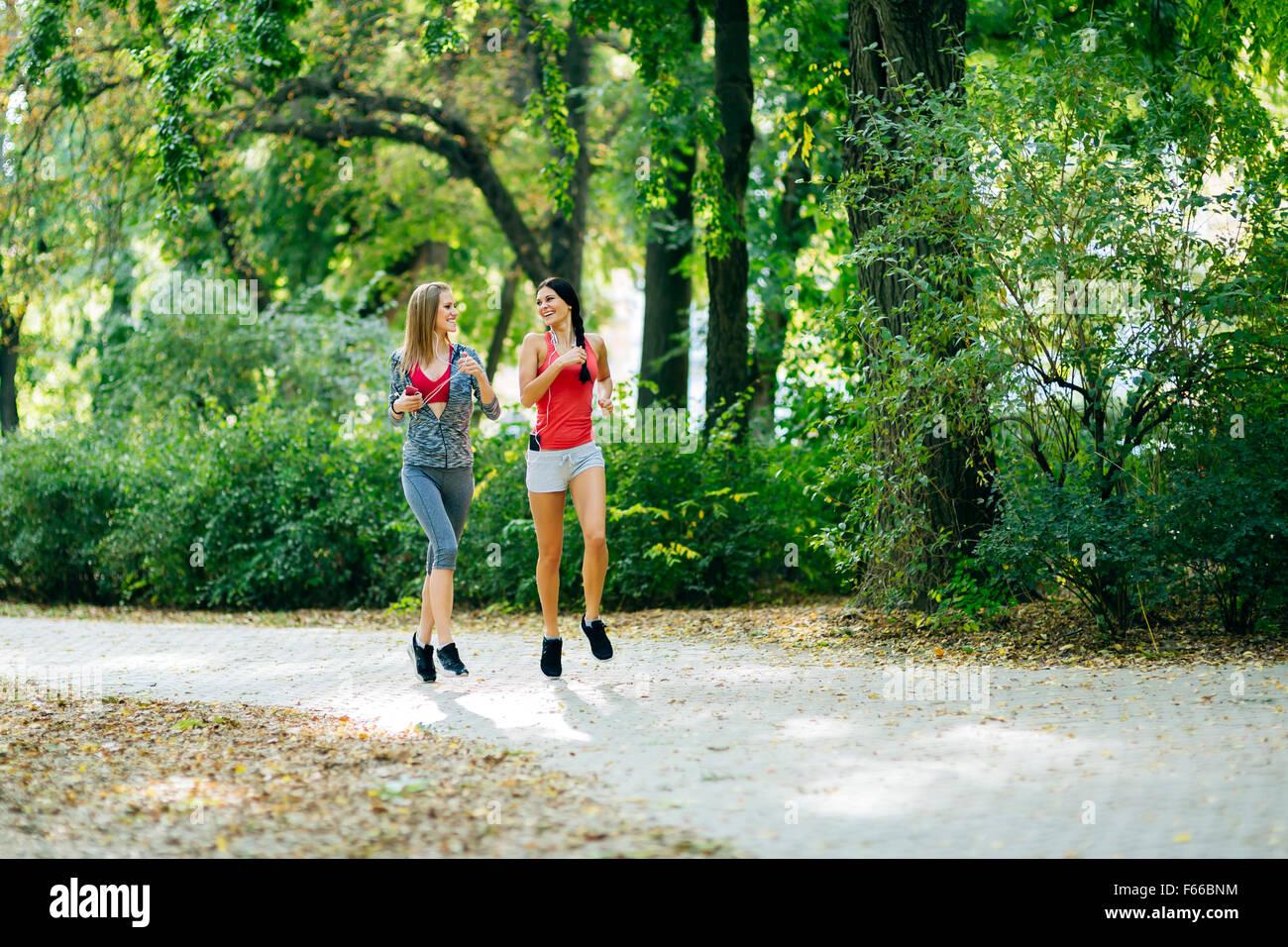 Beautiful sporty women jogging in park - Stock Image