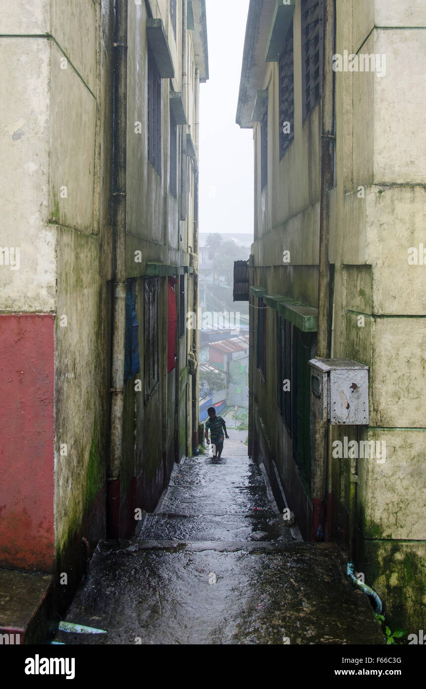 Child exploring city in alley way between high rise derelict buildings - Stock Image