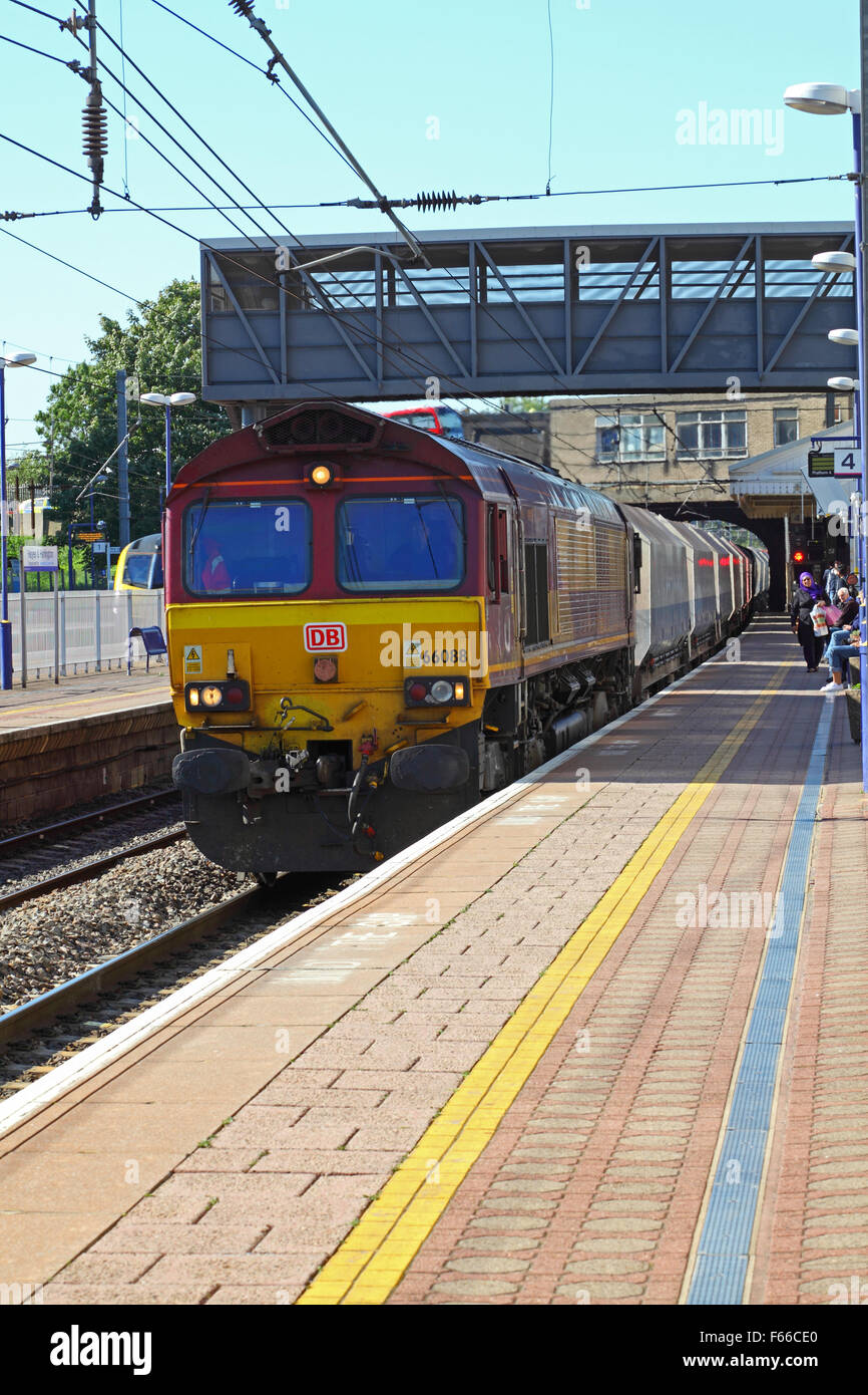 A class 66 Locomotive and trailing Ballast hoppers trundling along the platform at Hayes and Harlington towards - Stock Image