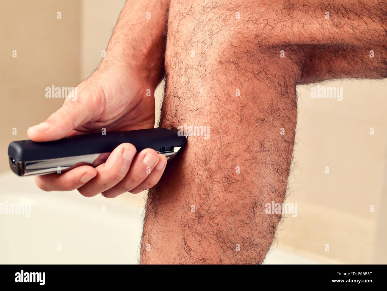 closeup of a young caucasian man trimming the hair of his legs with an electric trimmer Stock Photo