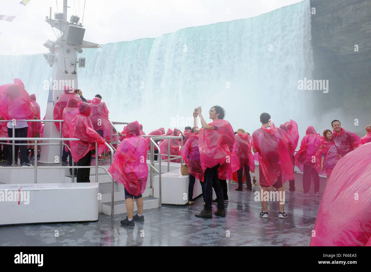 Tourists on the deck of the Canadian Hornblower boat riding close to Niagara Falls in Ontario. - Stock Image