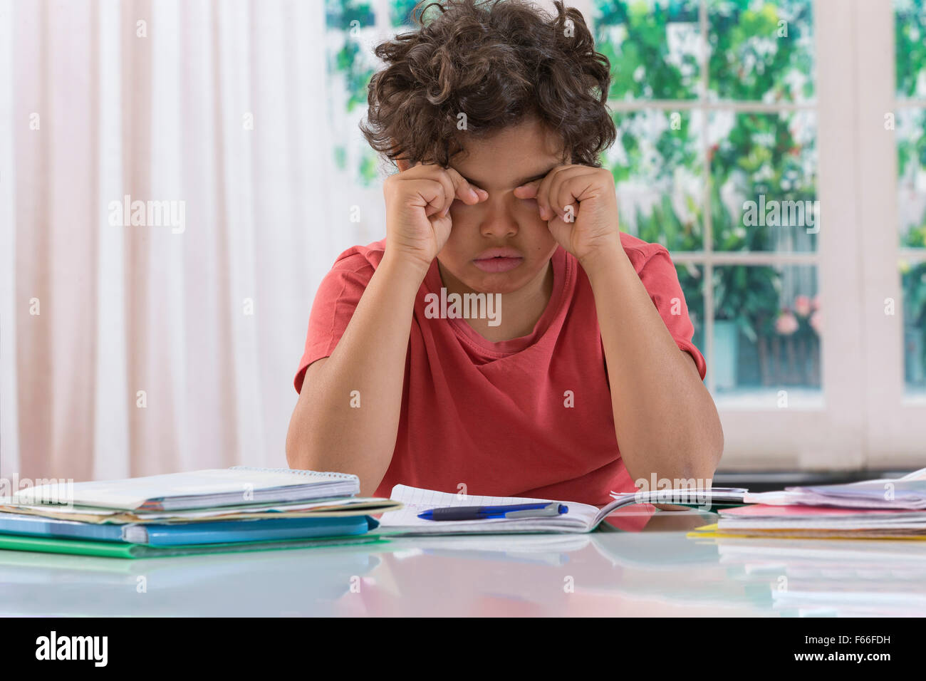 School boy rubbing eyes after long time homework - Stock Image