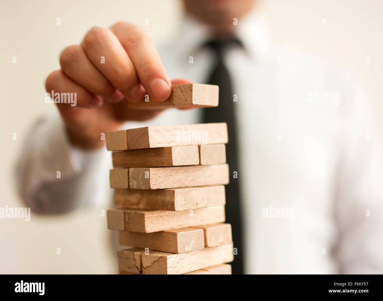 businessman builds a tower - Stock Image