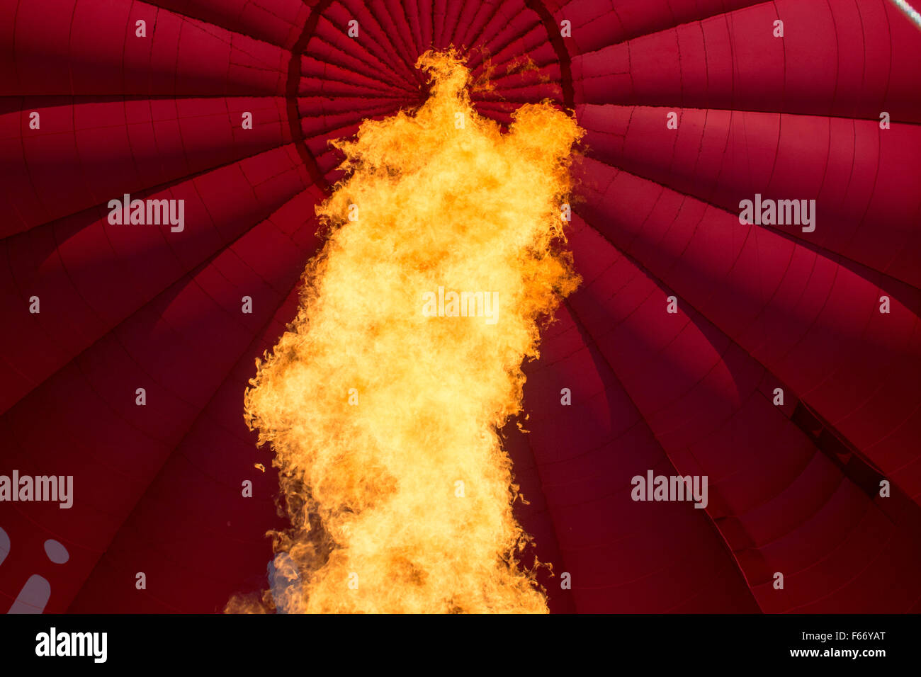Gas flame heating hot air balloon to help it rise. - Stock Image