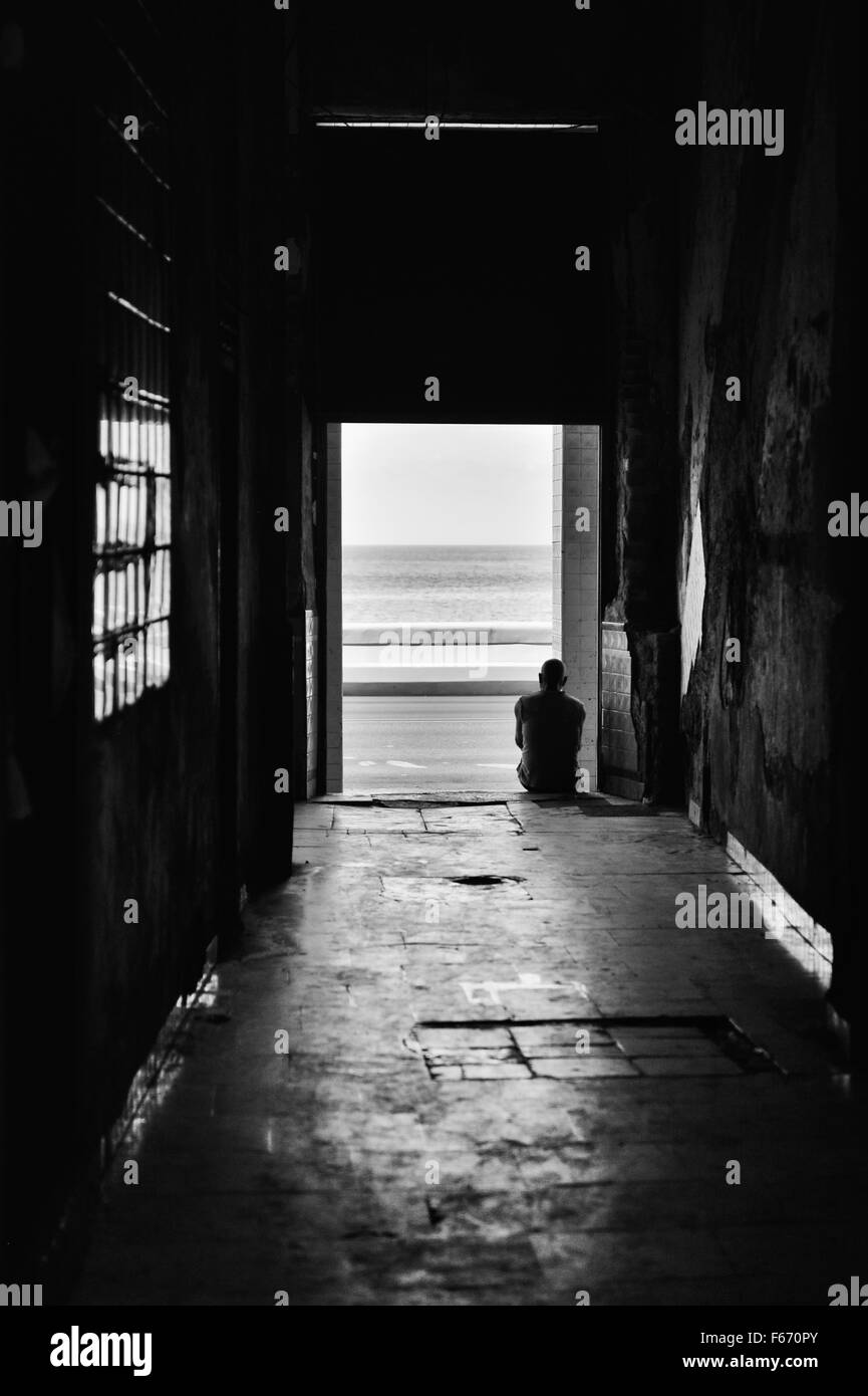 A seated silhouetted figure sits on the floor of a dark passage looking out onto The Malecon, Havana, Cuba. - Stock Image