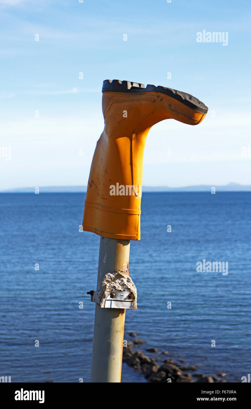 A single yellow rubber boot placed upside down on a wooden post. - Stock Image