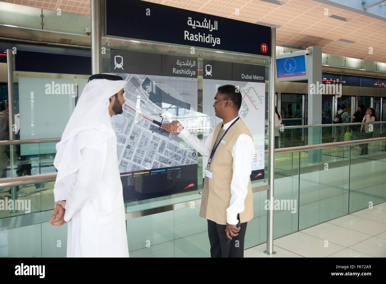 Arab man being given information from staff member of the Dubai Metro - Stock Image