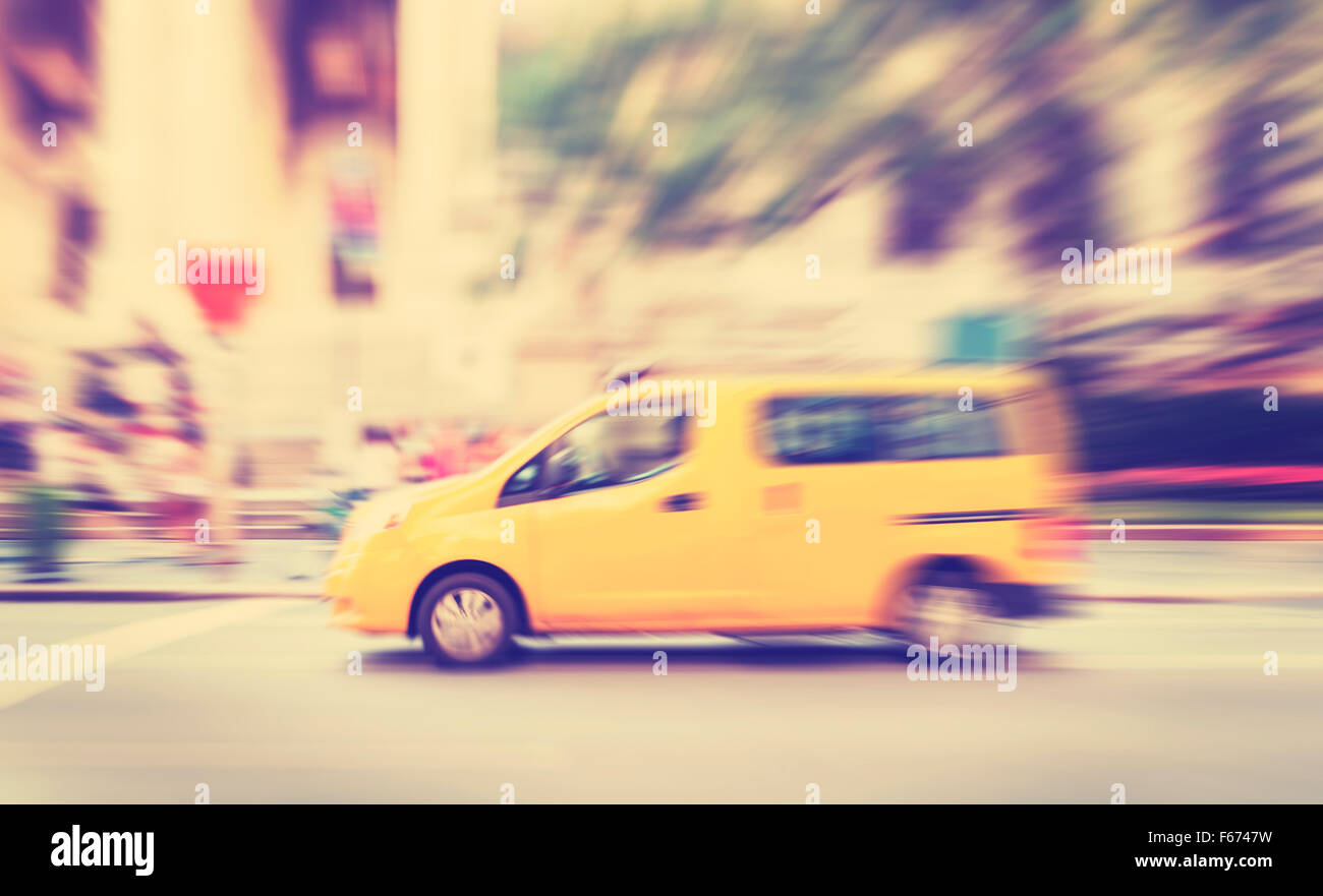 Vintage toned motion blurred yellow taxi on a street. - Stock Image