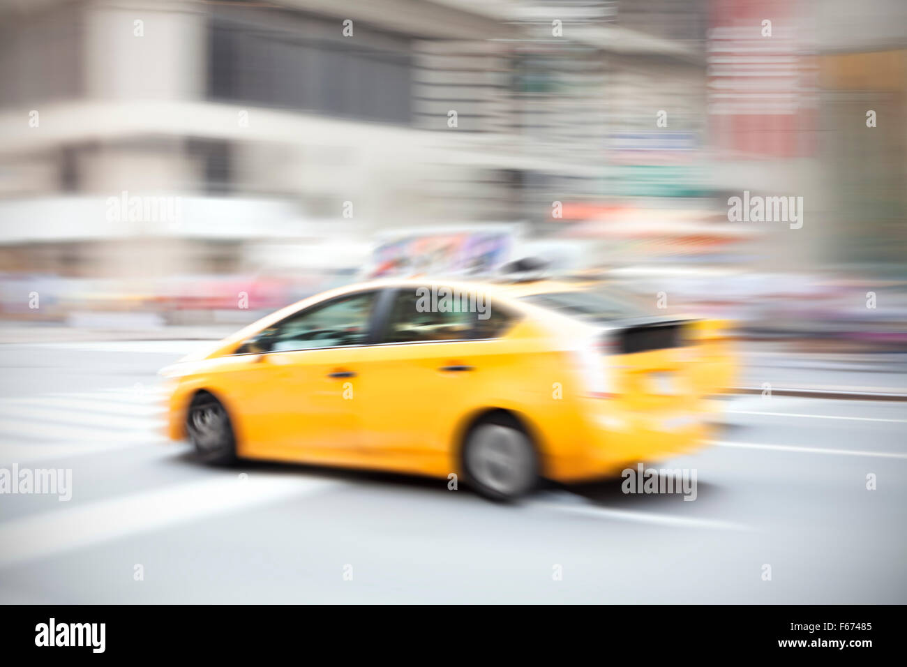 Motion blurred yellow taxi on a city street. - Stock Image