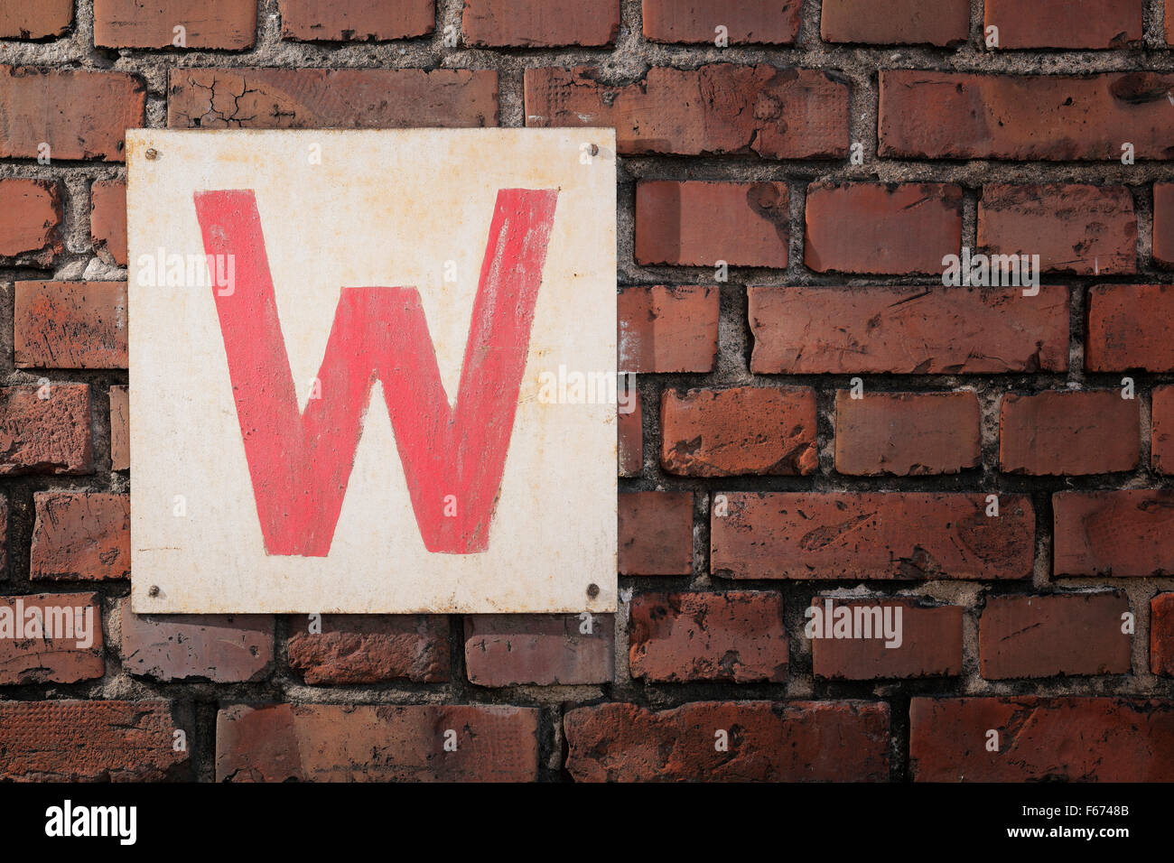 Old sign with letter W on a brick wall. Stock Photo