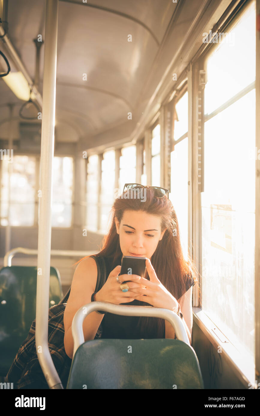 Half length of a young beautiful reddish brown hair caucasian woman using a smartphone on a tram - technology, social - Stock Image