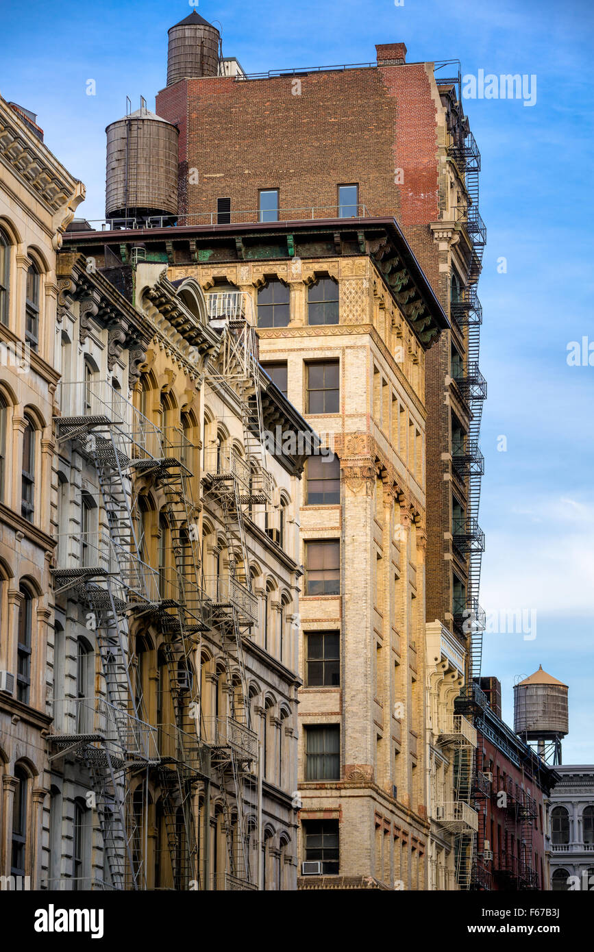 Soho loft buildings with fire escape and water towers on Broome Street, Manhattan, New York City. - Stock Image