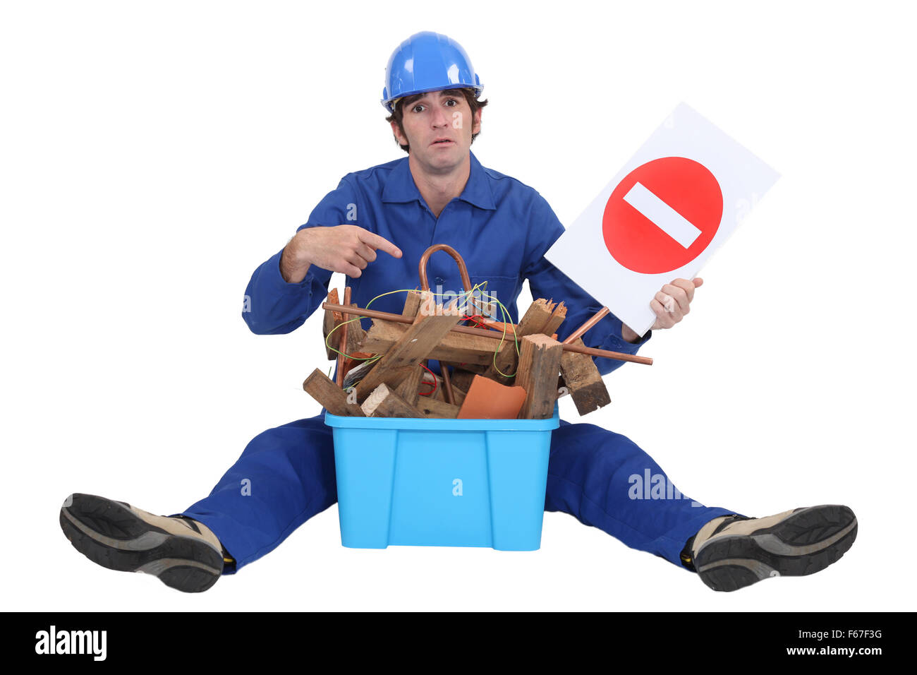 Worker with a box of old materials and a no entry sign - Stock Image