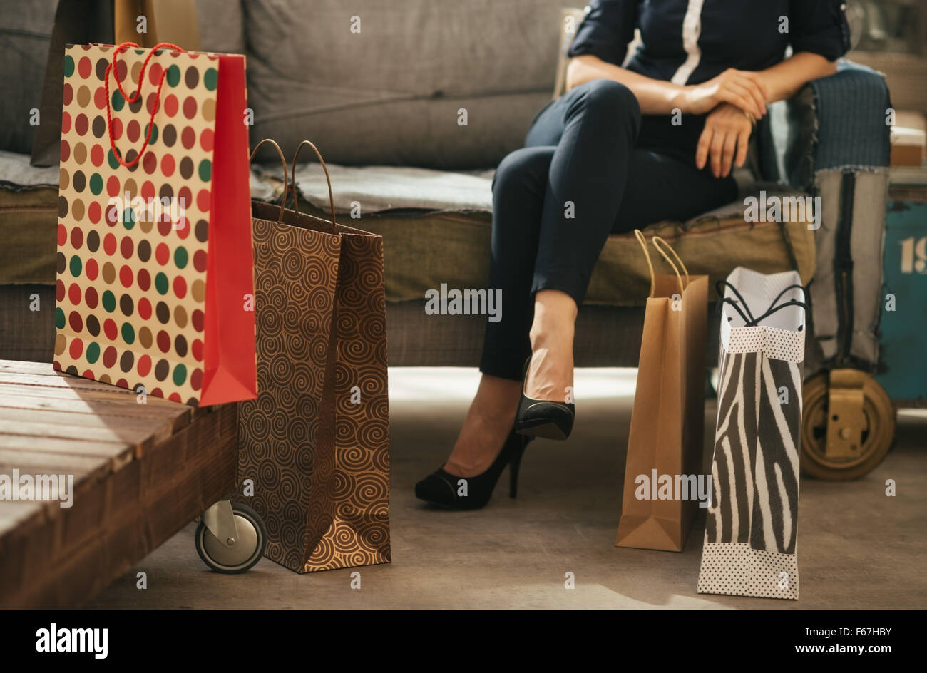 Close up on colourful shopping bags and elegant woman sitting on couch in modern loft apartment in background. Luxurious - Stock Image