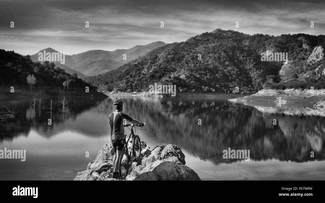 Mountain bike trail ride by a lake near the Pyrenees in Catalonia, Spain - Stock Image