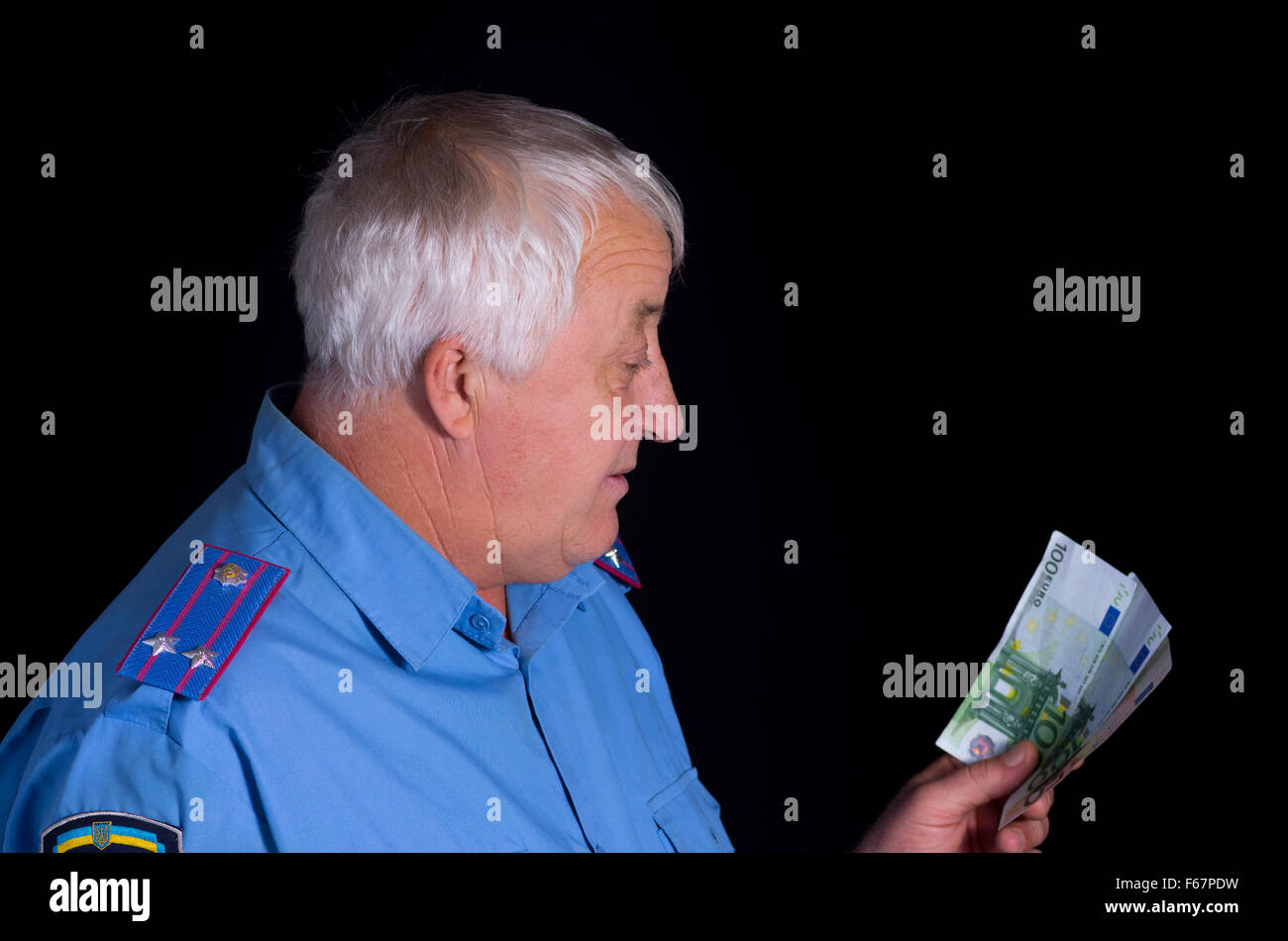 Portrait of police man looking on euro banknotes with interest - Stock Image