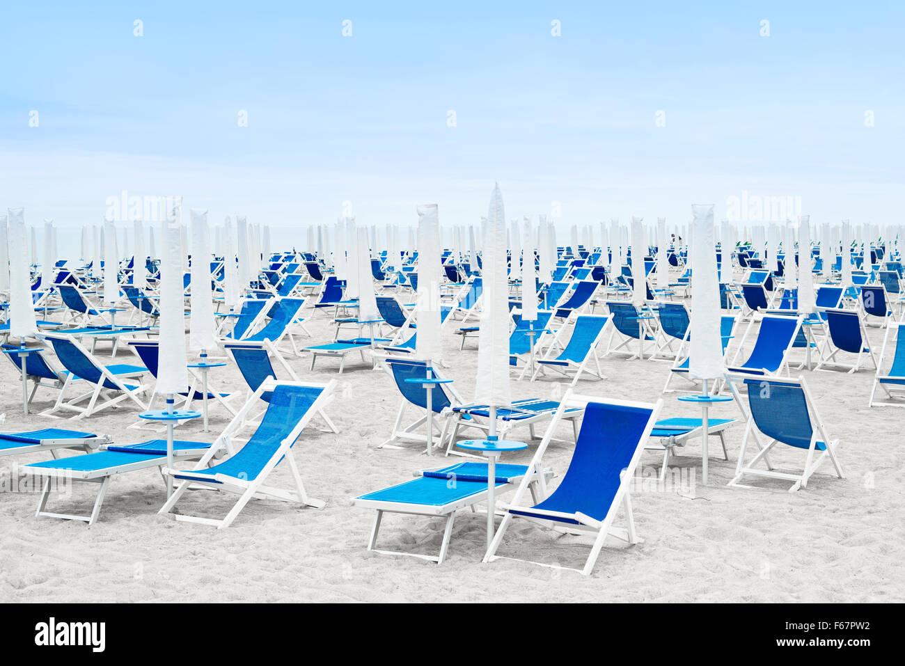 Beach umbrellas closed and blue deckchairs - Stock Image