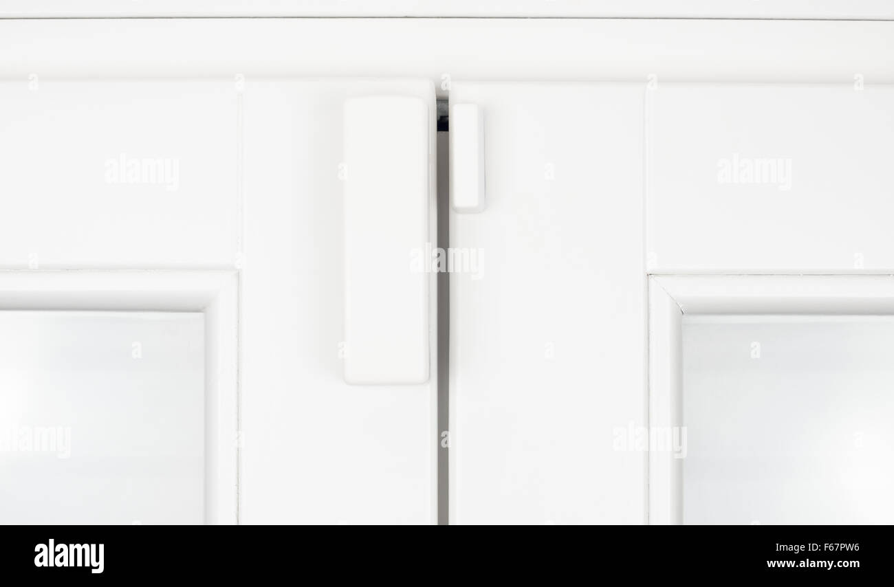 Wireless battery magnetic alarm sensor for window and door on white wooden sash detail - Stock Image