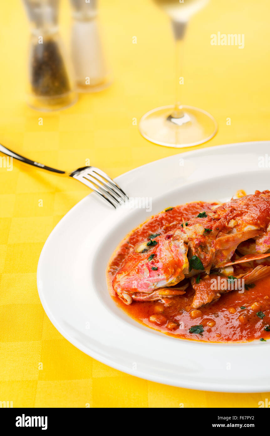 Red Mullets seafood italian traditional gourmet recipe with tomato, garlic, olive oil with wine glass, salt and - Stock Image