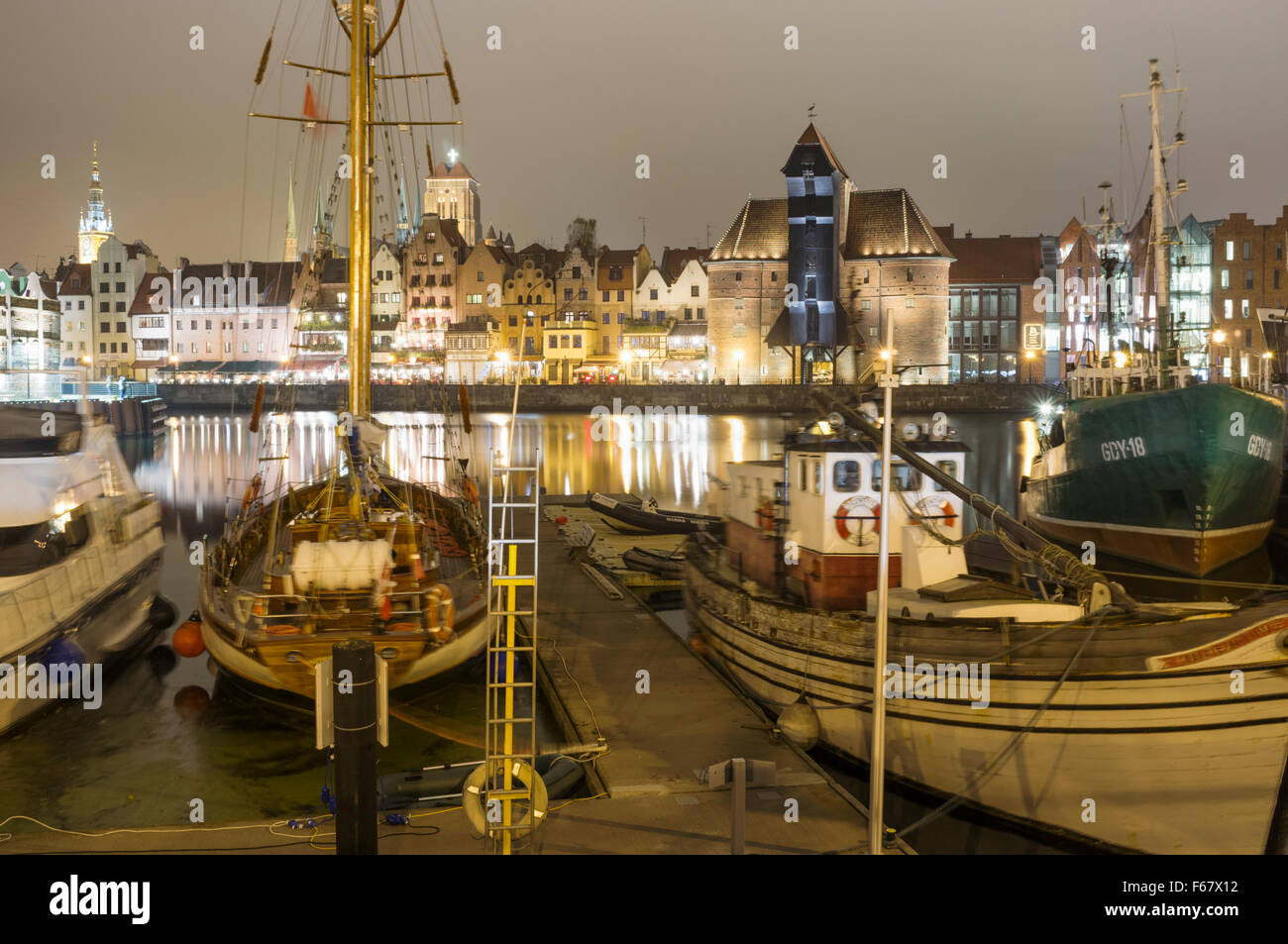 Anchored boats, medieval crane and waterfront tenements reflected on Motlawa river by night. Gdansk, Poland - Stock Image