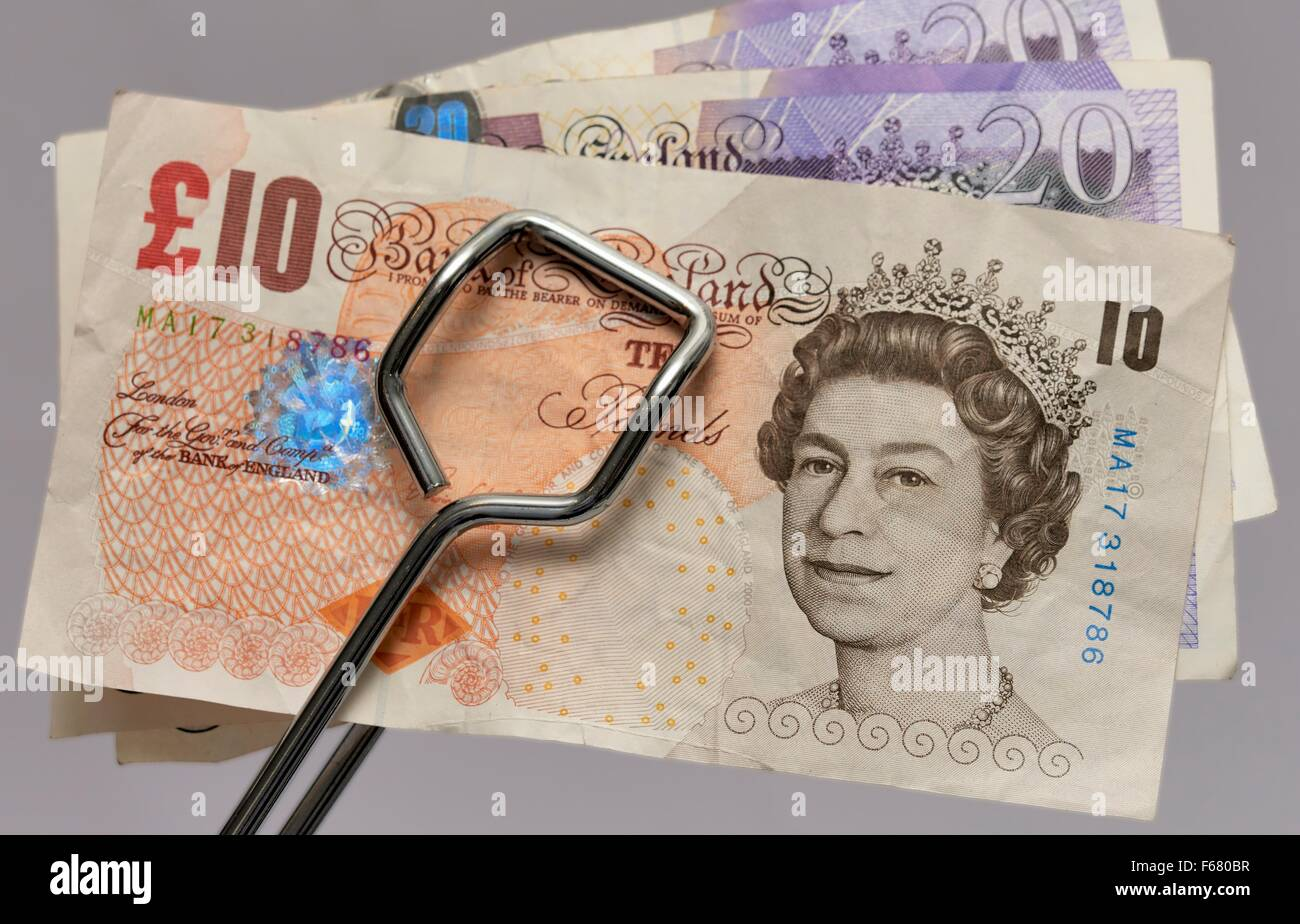 British 10 and 20 pound notes being held in metal tongs - Stock Image