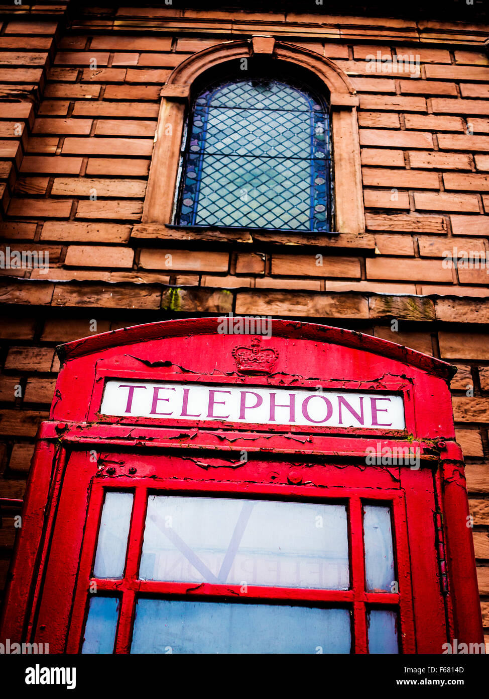 Low angled view of an old telephone kiosk outside Holy Trinity church in Warrington Town centre - Stock Image
