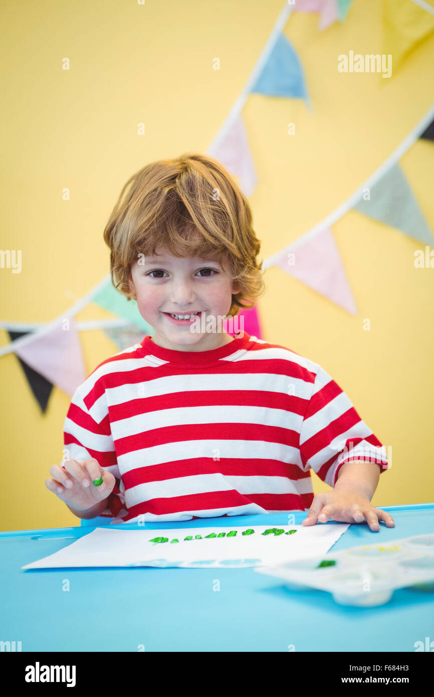 Smiling boy finger painting - Stock Image