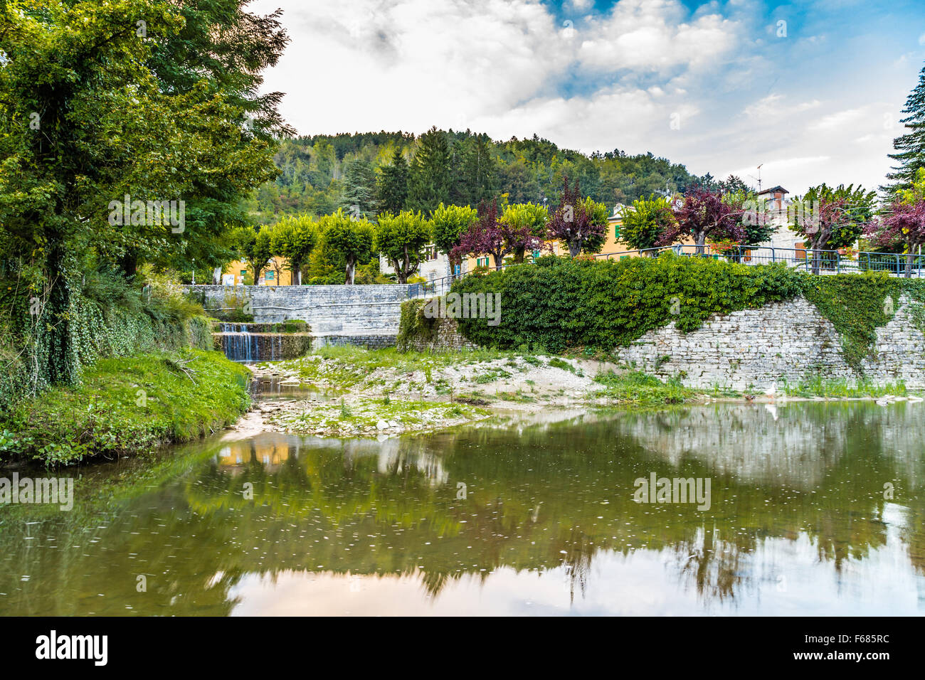 River runs thorugh medieval mountain village in Tuscany characterized by houses with walls of stones derived from Stock Photo