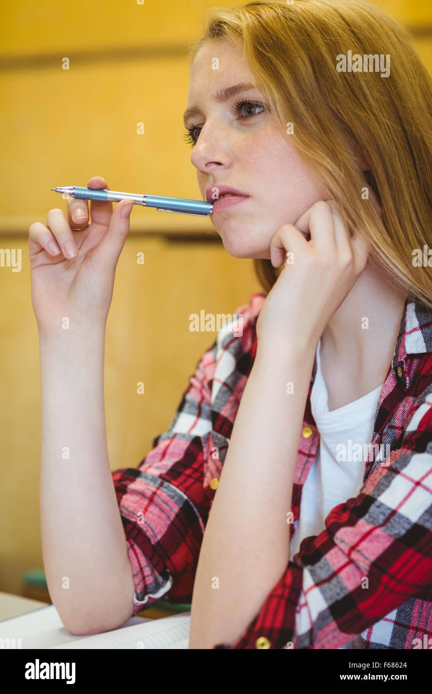 Unsure student holding pen during class - Stock Image